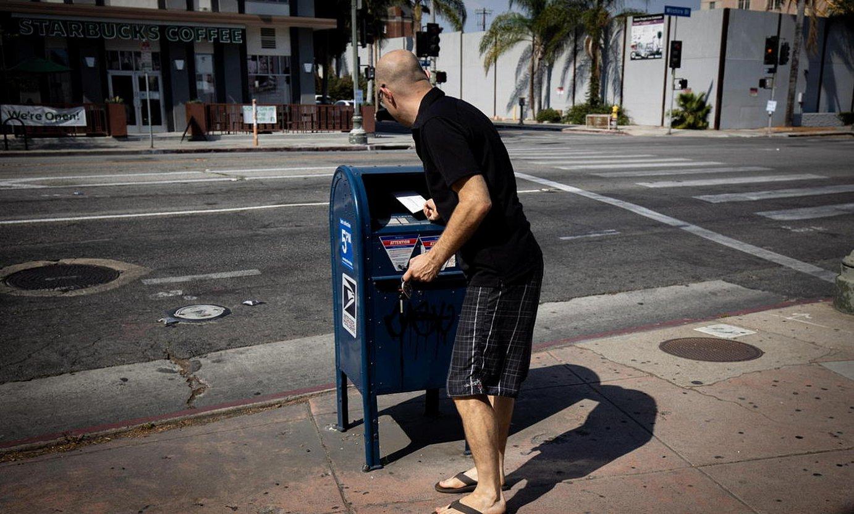 Gizon bat gutun bat botatzen Los Angelesko postontzi batean. / CHRISTIAN MONTERROSA / EFE