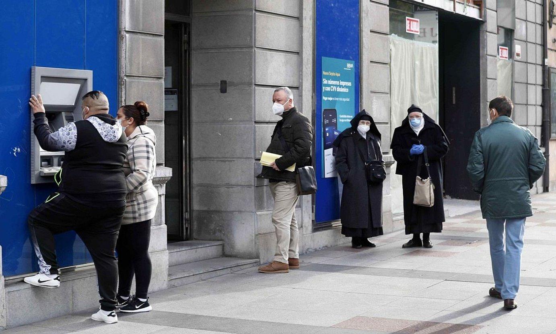 Herritarrak ilara egiten banku batean. ©CEREIJIDO / EFE
