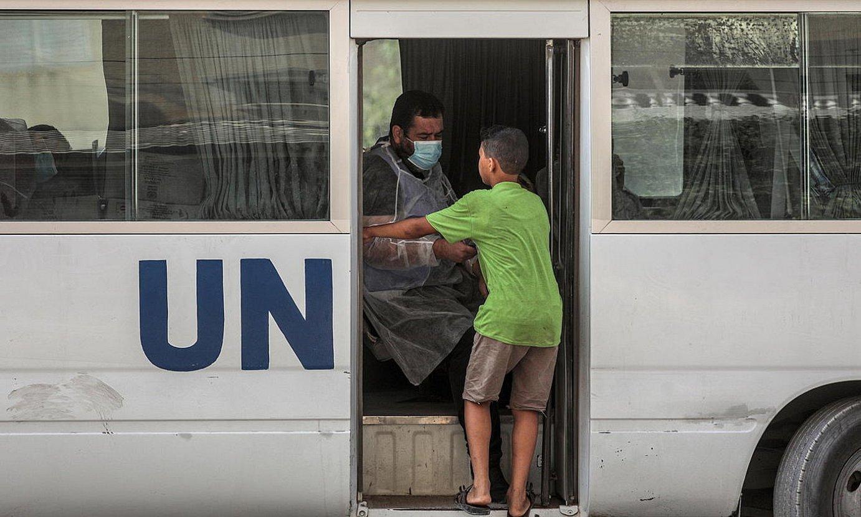 UNRWAko langile bat janaria banatzen Gazako herritarren artean. ©MOHAMMED SABER / EFE