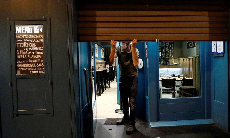 <b>Ostalari bat Iruñeko San Nikolas karrikako taberna batean, lanaldiaren ostean pertsiana jaisten. Aurrerantzean, 21:00etan itxi beharko dute atea.</b> ©JESUS DIGES / EFE