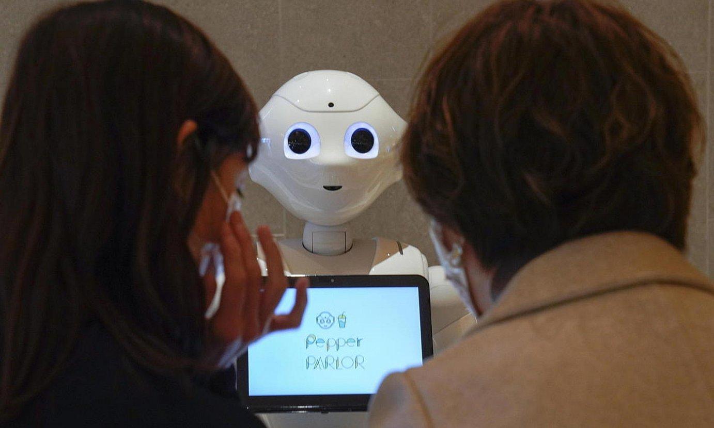 Bi pertsona robot baten aurrean. / KIMIMASA MAYAMA / EFE