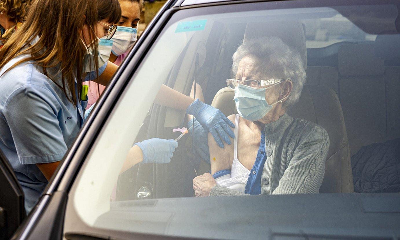 Osasun langile bat adineko bati txertoa jartzen autoaren barruan, Gasteizko Santiago ospitalean. ©J. FONTANEDA / FOKU