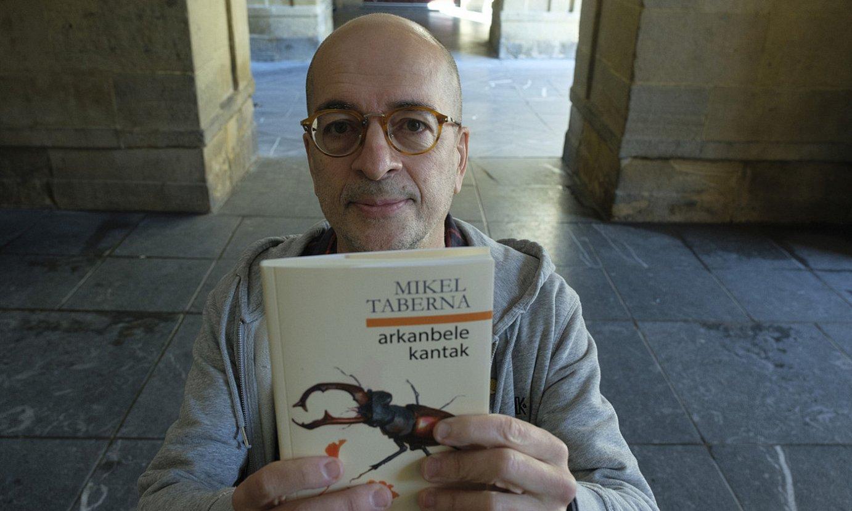 Mikel Taberna idazlea, atzo, <em>Arkanbele kantak</em> poema liburua hartuta, Donostiako Udal Liburutegiaren atarian. ©JON URBE / FOKU
