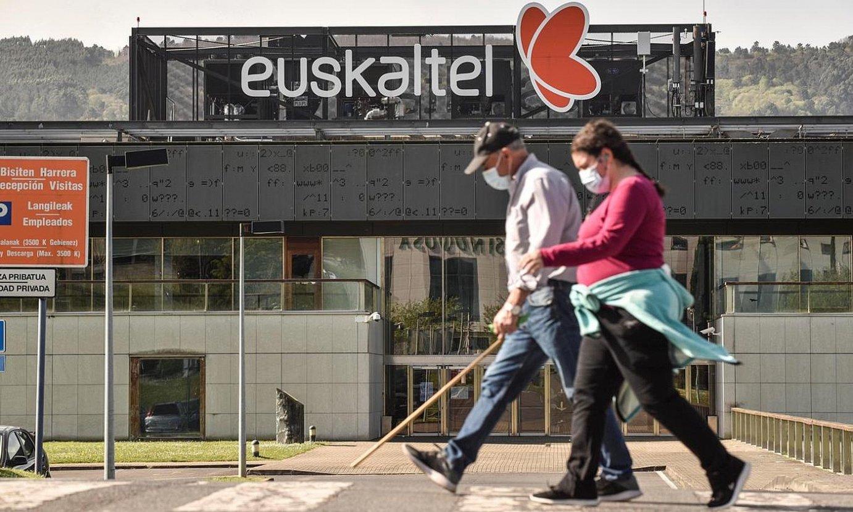 Bi pertsona Euskaltelek Derioko parke teknologikoan (Bizkaia) duen egoitzaren aurrean paseatzen, atzo. ©MIGUEL TOÑA / EFE