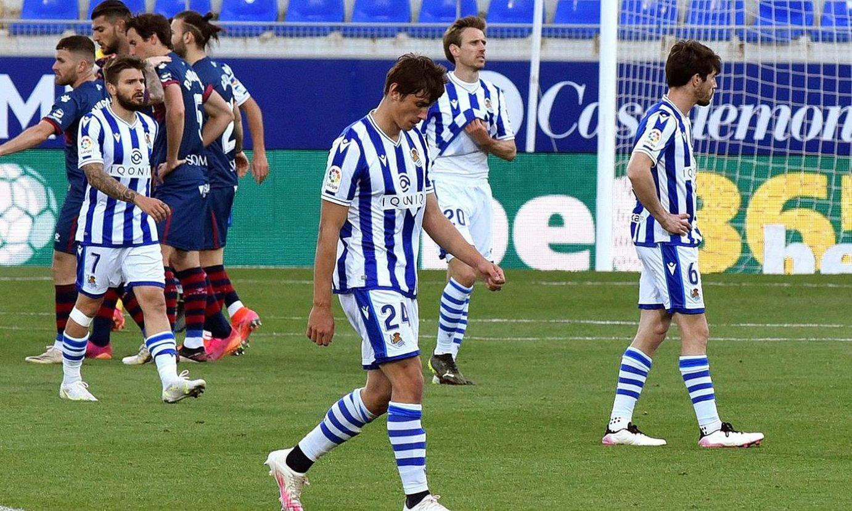 <b>Realeko hainbat jokalari burumakur, eta atzean, Huescakoak, pozarren, atzoko gol bakarra sartu berritan.</b> ©JAVIER BLASCO / EFE