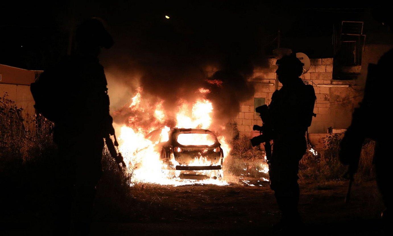 Israelgo soldadu batzuk, sutan dagoen auto bati begira, herenegun, Jerusalemen. ©ABIR SULTAN / EFE