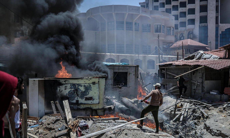 Pertsona bat Israelen bonbardaketek eragindako sua itzaltzen saiatzen, atzo, Gazan. ©MOHAMMED SABER / EFE