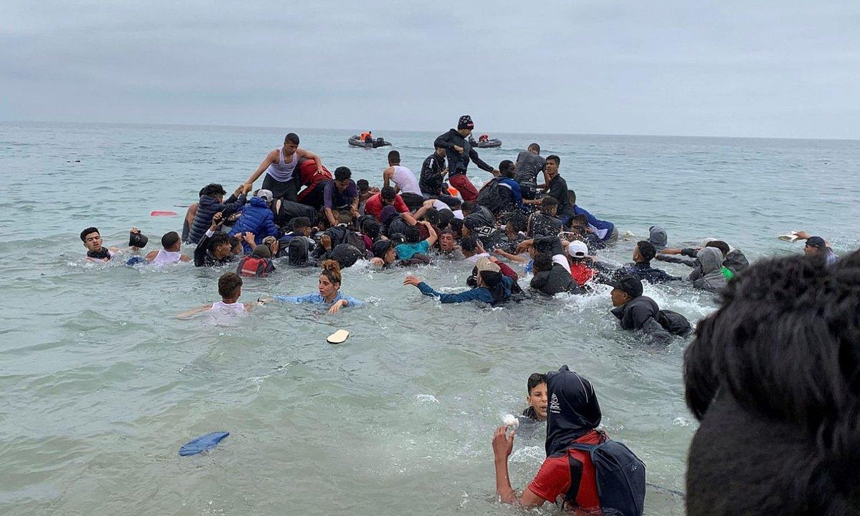 Migratzaile talde bat, Marokoko segurtasun indarren ontzi batera igotzen, Ceutako uretara igaro ahal izateko. ©MOHAMED SIALI / EFE