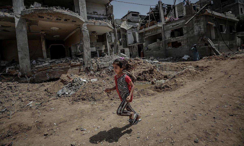 Haur bat suntsitutako eraikinen hondakinen artean korrika, joan den astean, Gazan. ©MOHAMMED SABER / EFE