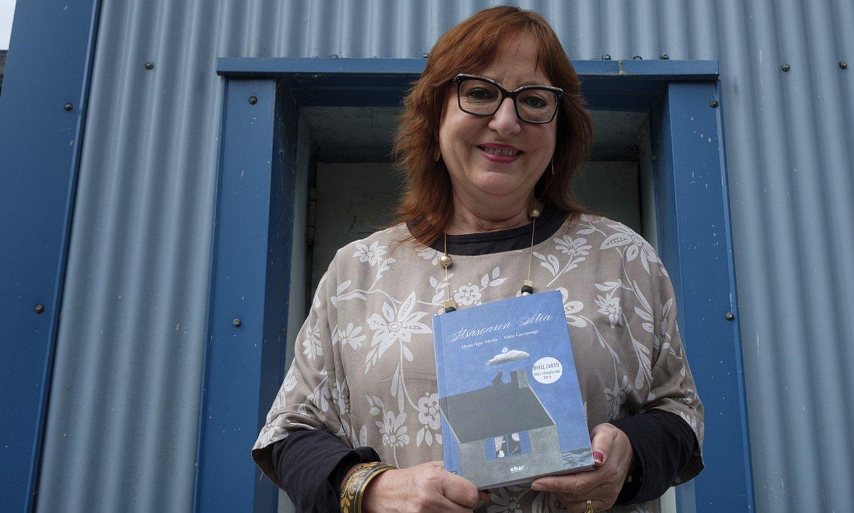 Miren Agur Meabe idazlea, <em>Itsasoaren atea</em> liburua eskuetan duela. ©JON URBE / FOKU