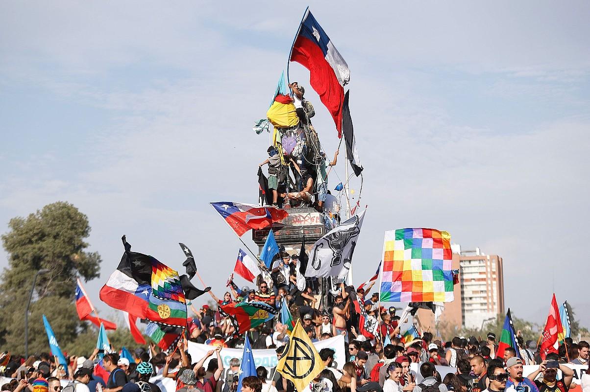 2019ko urriaz geroztik protestariek bere egin dute Santiago hiriburuko Italia plaza, eta <em>Duintasun plaza</em> deitzen diote orain. Irudian, Manuel Baquedano jeneralaren estatuaren gainean, 2019ko abenduan. ©ALBERTO VALDES / EFE