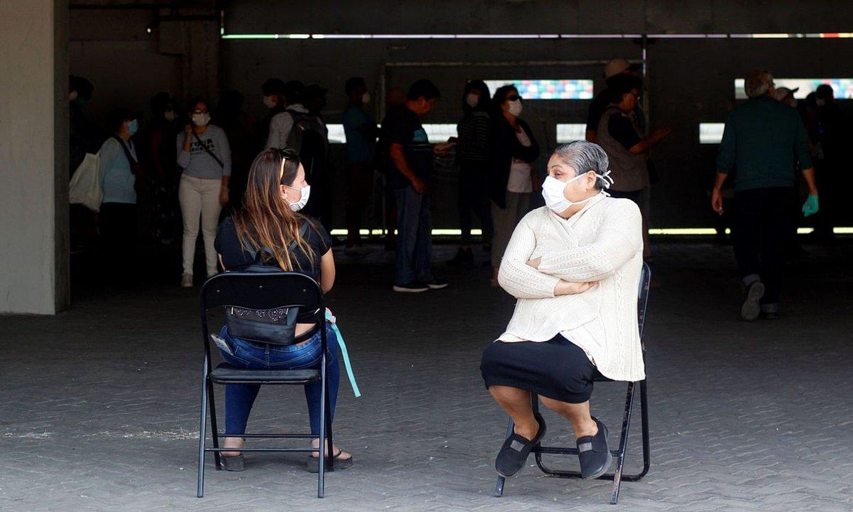 Bi lagun COVID-19aren aurkako txertoa hartzeko zain, Santiagon, Txilen. ©SEBASTIAN SILVA / EFE
