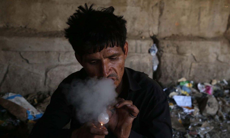 Gizon bat opioa erretzen, Jalalabaden. ©GHULAMULLAH HABIBI / EFE
