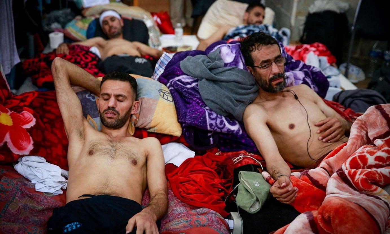 Gose greba egiten ari ziren bi migratzaile, Bruselako San Joan Bataiatzailearen elizan. ©STEPHANIE LECOCQ / EFE