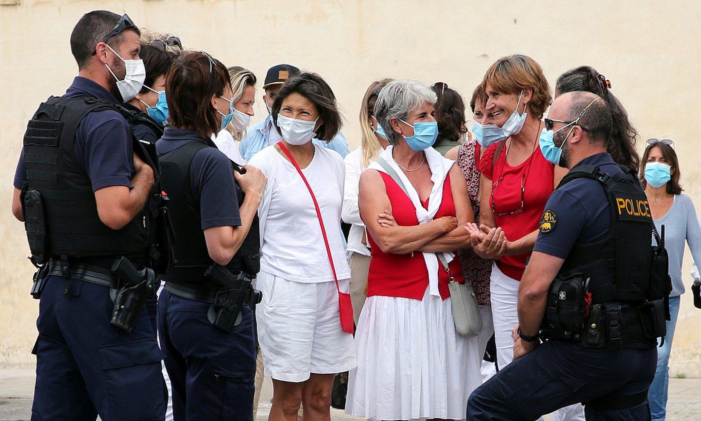 Zuriz eta gorriz jantzitako hiru emakume, Frantziako Poliziak inguratuta, atzo, Baionan. ©BOB EDME
