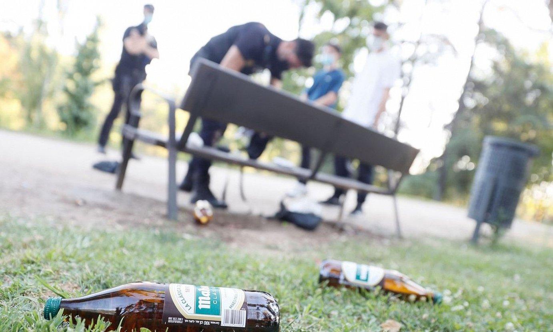 2021-07-04. Madril. Polizia kaleko edanean ari ziren gazte batzuk miatzen, Madrilgo Mendebaldeko parkean. ©MARISCAL / EFE