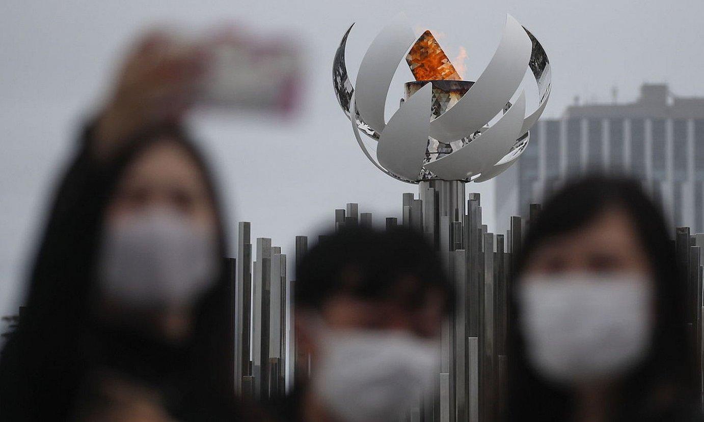 Bisitari batzuk, Tokioko Olinpiar Jokoetako suontziaren aurrean argazkiak ateratzen. ©FAZRY ISMAIL / EFE