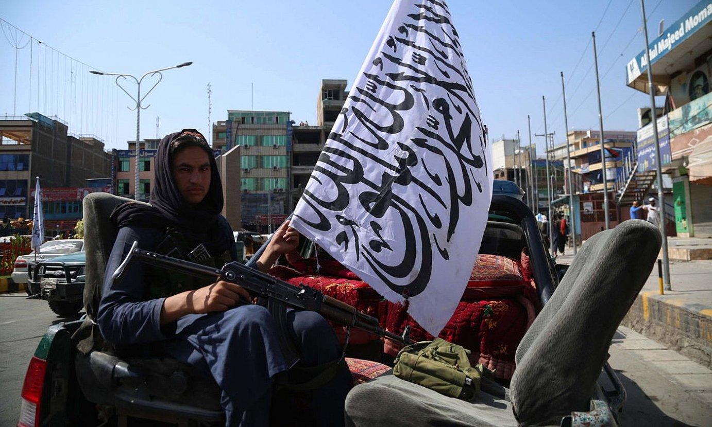 Taliban bat ibilgailu batean, taldearen bandera eta arma bat eskuetan dituela, Jalalabaden. ©STRINGER / EFE
