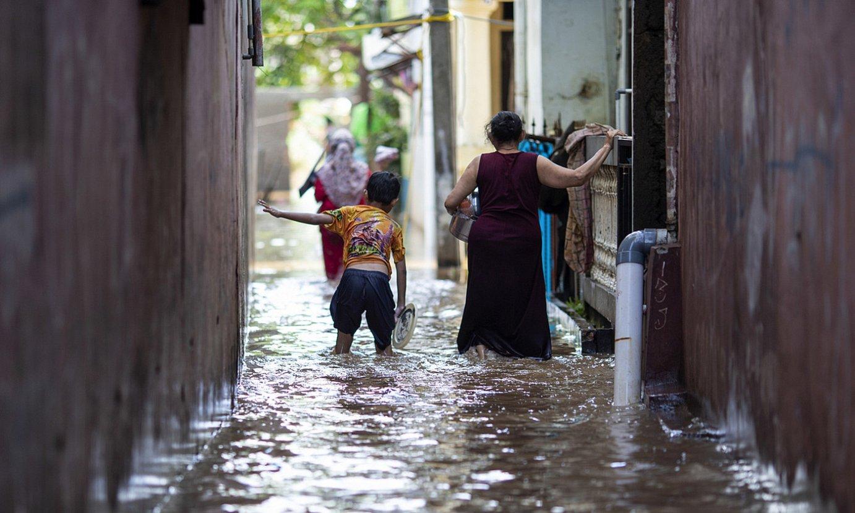 Bi pertsona hankak uretan dituztela, Jakartan, iragan otsailean. ©UNICEF