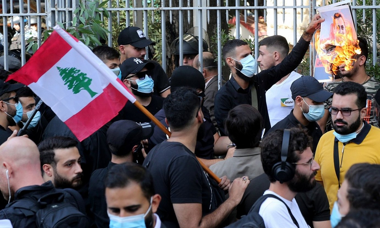 Militante xiitak, atzo Beiruten egindako manifestazioan. Horietako bat, Tarek Bitar epailea azaltzen den argaki bati su ematen. ©NABIL MOUNZER / EFE