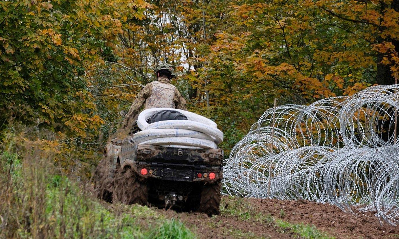 Letoniako armadako soldadu bat, Bielorrusiarekiko mugan, burdin harizko hesi labanaduna altxatzen. ©VALDA KALNINA / EFE